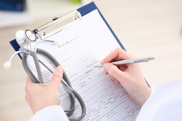 Female doctor hand holds silver pen filling patient list at clipboard pad closeup.
