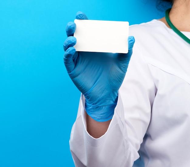 Рука женщины доктора в голубых медицинских латексных перчатках держит пустую бумажную визитную карточку