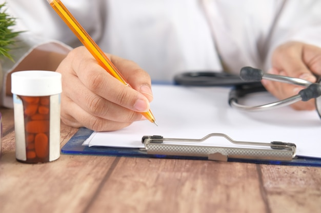 Female doctor hand writing prescription on desk close up