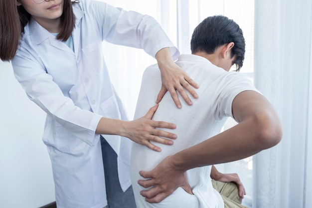 Female doctor hands doing physical therapy by extending the back of a male patient.