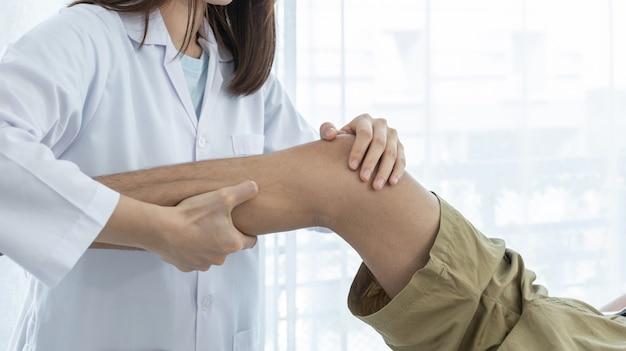 Женщина-врач вручает физиотерапию, разгибая ногу и колено пациента мужского пола.