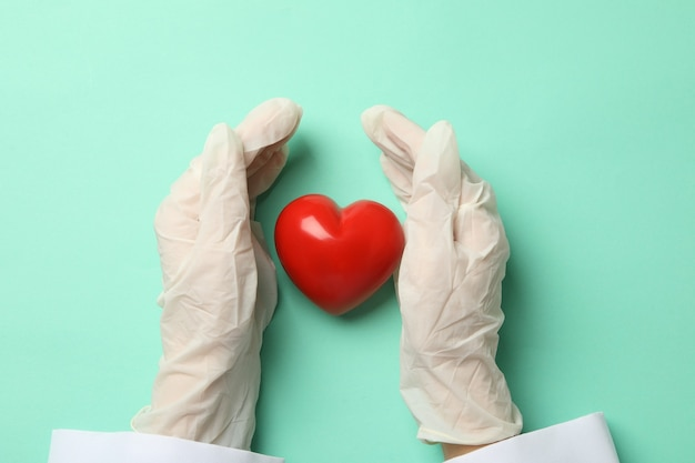 Female doctor hands in gloves and heart on mint surface