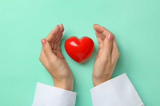 Female doctor hands and heart on mint