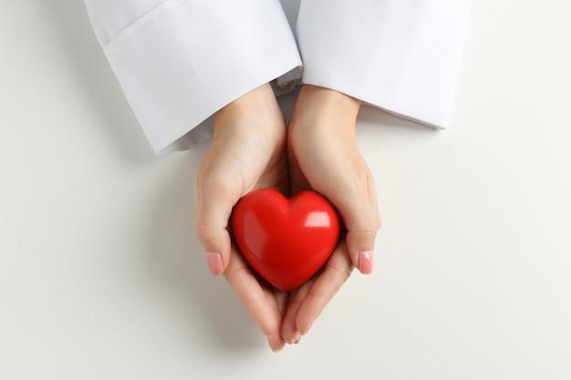 Женщина-врач руки держит сердце на белой поверхности