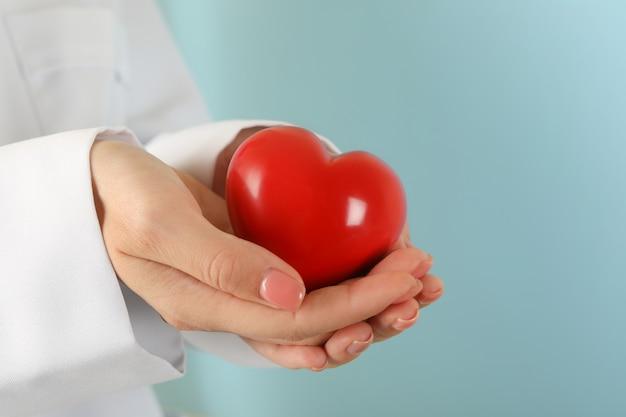 Женщина-врач руки держит красное сердце