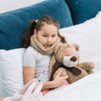Female doctor hands spraying the syringe with medicine in front of sick girl sitting with teddy bear on bed