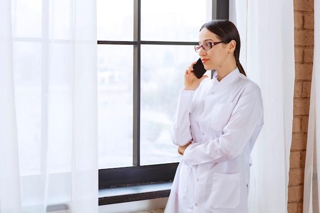 Женщина-врач, имеющая важный телефонный звонок возле окна.