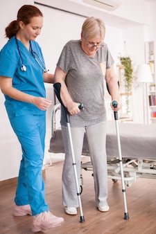 Female doctor helping old woman with crutches in nursing home.