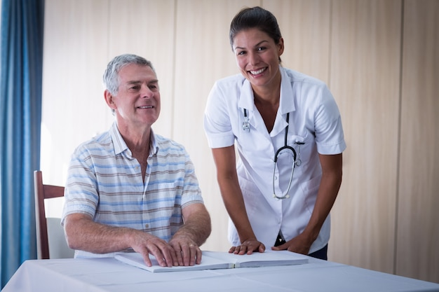 Female doctor helping patient in reading the braille book