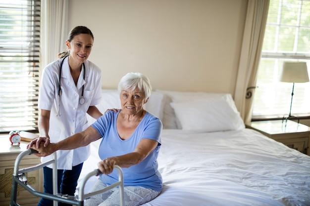 年配の女性が自宅で歩行器と一緒に歩くのを助ける女医