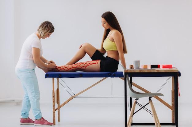 女医は彼女の足にキネシオテープを貼ることによって女性を助けます。彼女の足に運動学弾性治療テープを持つ若い白人女性