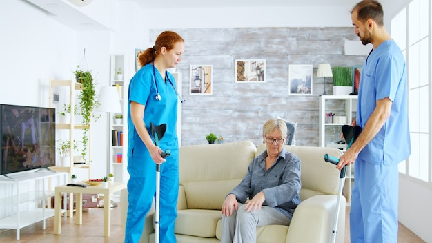 Female doctor and her assistant helping old woman with crutches to stand up from the couch and take a walk