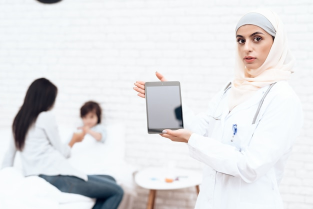 A female doctor in hijab posing on camera.