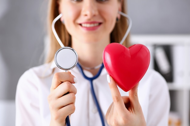 Female doctor hold in arms red heart and phonendoscope