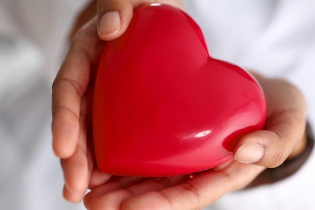 Женщина-врач держит в руках и красную крышку