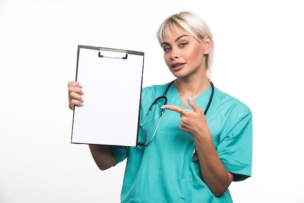 흰 벽에 클립 보드 가리키는 손가락을 들고 여성 의사.