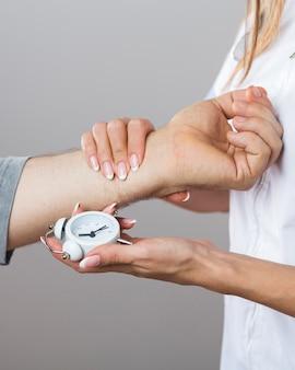 Женский доктор держа часы и терпеливую руку