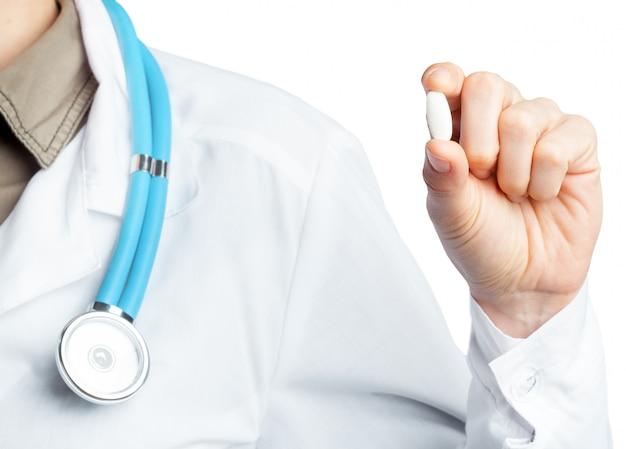 Женский доктор, держа таблетки. изолированные на белом.