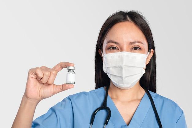 Женщина-врач держит бутылку вакцины