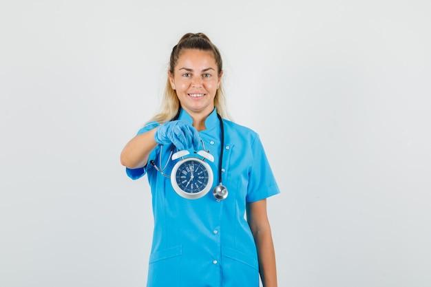 青い制服を着た目覚まし時計を保持している女性医師