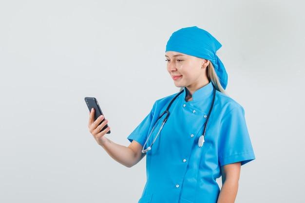 Женщина-врач холдинг и глядя на смартфон в синей форме и выглядит веселым.