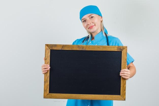 黒板を持って青い制服を着て笑っている女医師