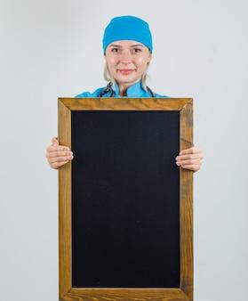Medico femminile che tiene lavagna e sorridente in uniforme blu