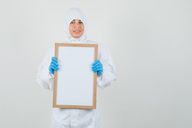 Medico femminile che tiene cornice vuota in tuta di protezione