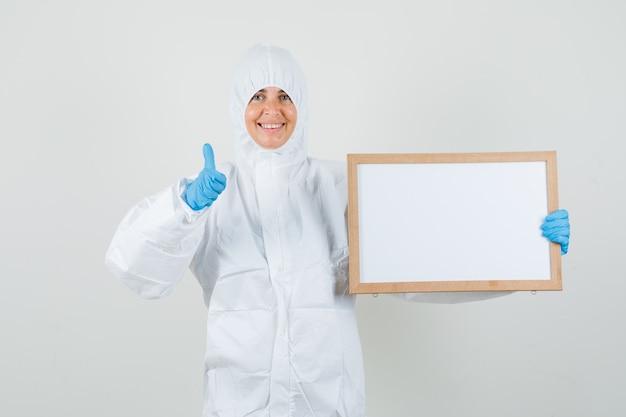 Medico femminile che tiene cornice vuota con il pollice in su in tuta protettiva