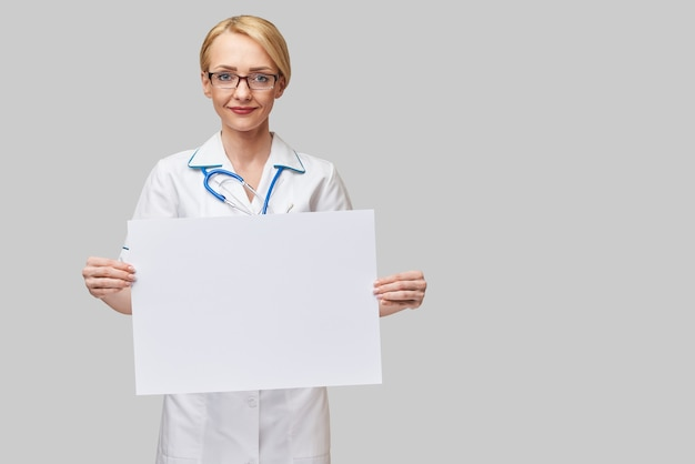 Female doctor holding a blank paper sheet or poster.
