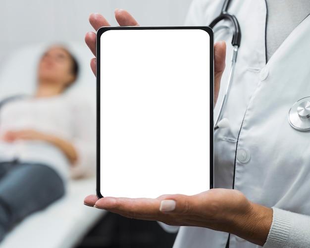 Medico femminile che tiene una compressa in bianco