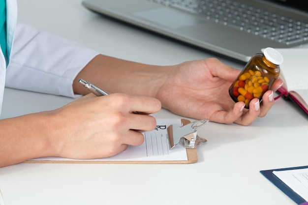 錠剤と処方箋を書くボトルを保持している女性医師のクローズアップ