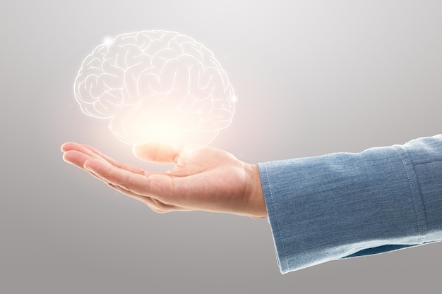 Женщина-врач держит иллюстрацию мозга на сером фоне. защита и уход за психическим здоровьем.
