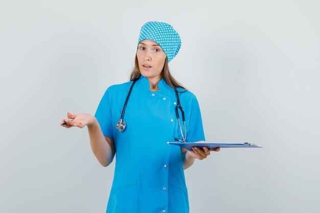 青い制服を着てクリップボードとペンを保持し、混乱しているように見える女性医師。正面図。