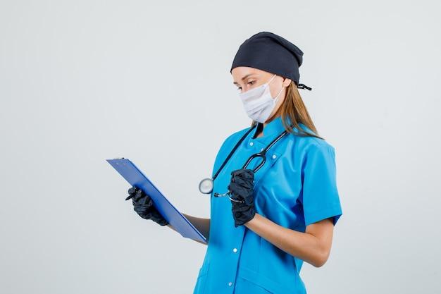Женщина-врач, держащая буфер обмена и стетоскоп в униформе, перчатках, маске и выглядящая занятой.