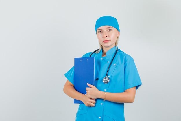 青い制服でクリップボードを保持している女性医師