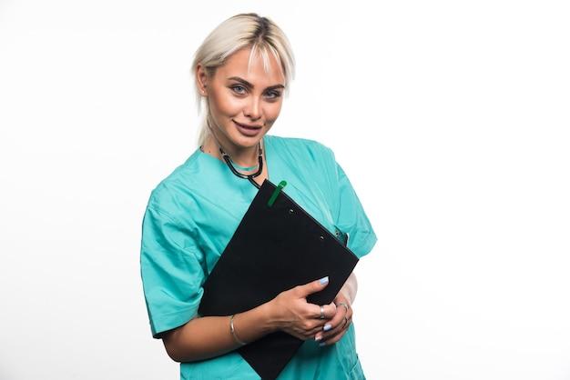 흰 벽에 클립 보드를 들고 여성 의사입니다.
