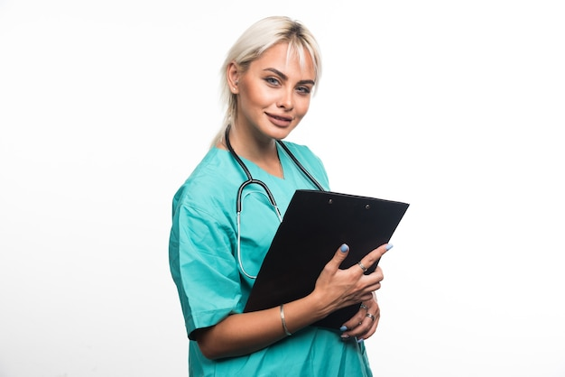 Medico femminile che tiene appunti su superficie bianca