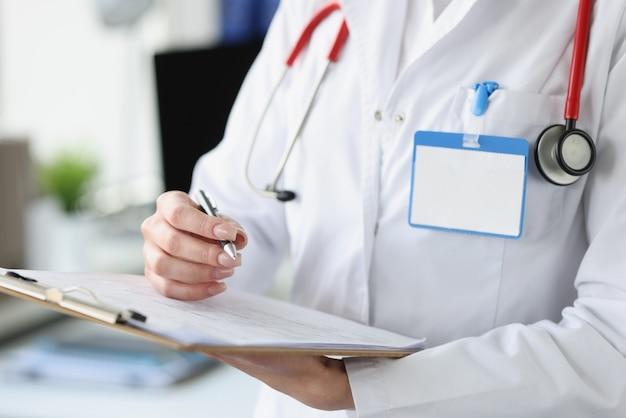 그녀의 손에 근접 촬영 문서와 볼펜 클립 보드를 들고 여성 의사
