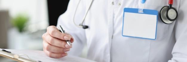 Женщина-врач держит буфер обмена с документами и шариковой ручкой в руках крупным планом