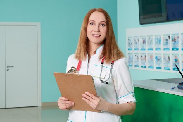 Женщина-врач, держащая буфер обмена с записями. медицинское обслуживание, страховка, рецепт, медицинская бумага