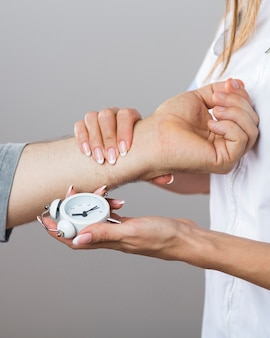 Female doctor holding a clock and patient hand