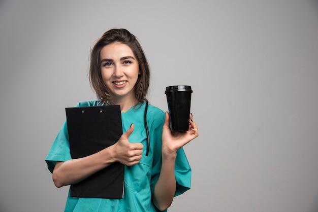 Женщина-врач, держащая кофейную чашку и доску сзажимом для бумаги. фото высокого качества