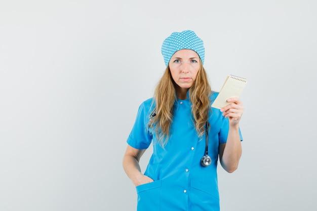 青い制服を着たポケットに手でコピーブックを保持している女性医師