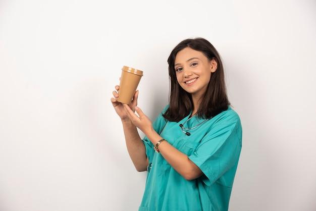 Женщина-врач, держа чашку кофе на белом фоне. фото высокого качества