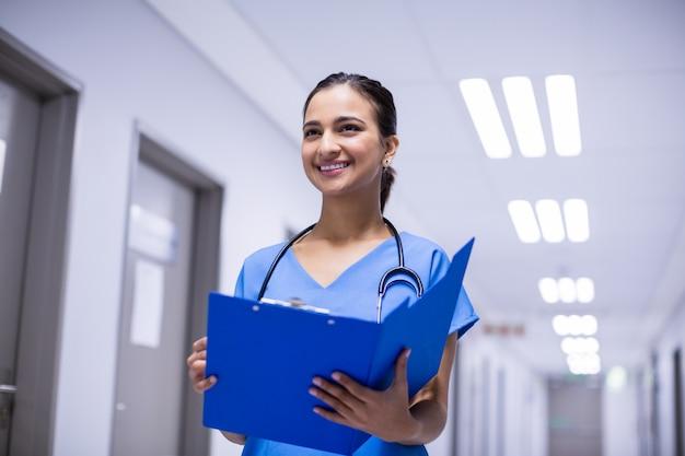Female doctor holding file in corridor
