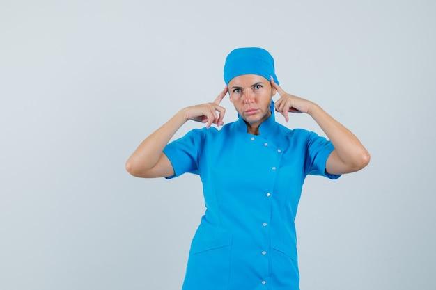 青い制服を着た寺院に指を持ち、思慮深く、正面から見ている女性医師。