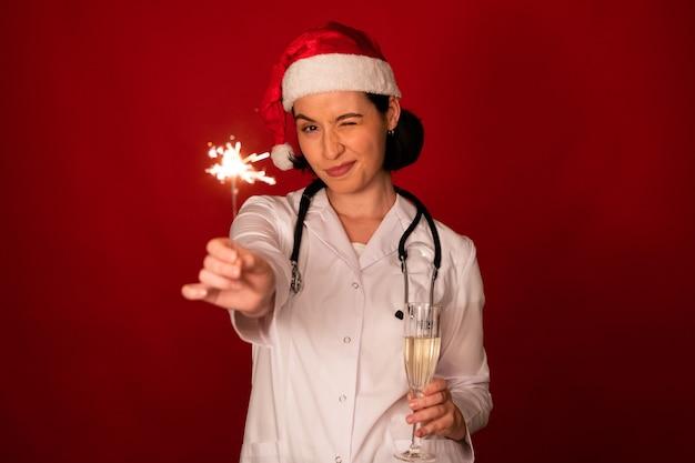 여성 의사 샴페인 잔을 들고 그녀의 손에 폭죽을 굽기