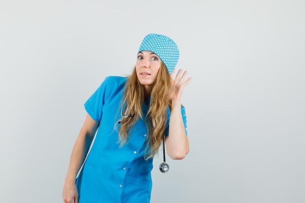 Medico donna tenendo la mano dietro l'orecchio in uniforme blu e guardando curioso