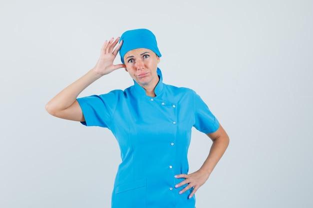 Medico femminile che tiene la mano a testa in uniforme blu e che sembra confuso. vista frontale.